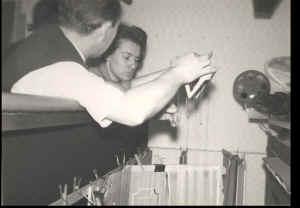 """Albert Vermeiren en echtgenote achter de schermen. Let op de massa aan papierklemmen om de ingewikkelde decors recht te houden ; bemerk ook het merkwaardige speelkruis en de vele """"bolletjes"""" in de draadjes .."""